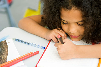 Little girl resting head on desk, drawing on graph paper - p62314861f by Michele Constantini