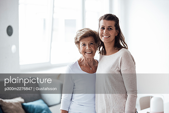 Happy senior woman with granddaughter standing together at home - p300m2276847 by Gustafsson