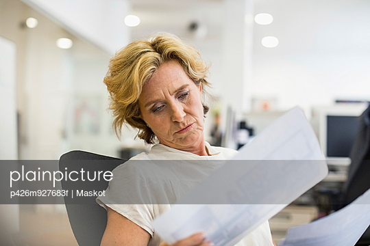 Relaxed businesswoman reading documents in office