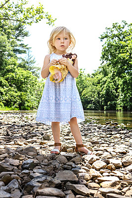 Little girl with doll on the riverbank of Cedar Creek - p1019m1462183 by Stephen Carroll