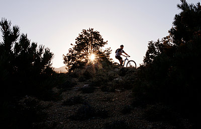 Man cycling on mountain during sunset - p1166m1231664 by Cavan Images
