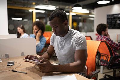Black worker using tablet in office - p1166m2234851 by Cavan Images
