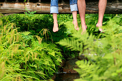 Couple with feet dangling over wooden bridge in forest.  - p1328m1165901 by Pierre Desrosiers