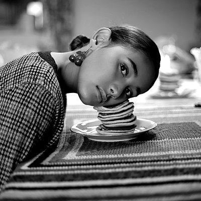 Girl with face on a pile of pancakes - p1521m2128978 by Charlotte Zobel