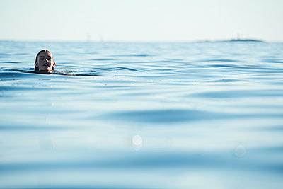 Teenage girl swimming in sea - p312m1211153 by Johan Alp