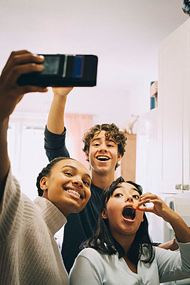 Cheerful friends taking selfie while eating at home - p426m2145482 by Maskot