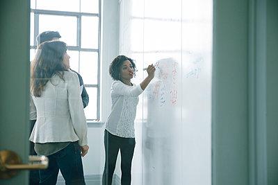 Businesswoman writing on whiteboard in meeting - p555m1504088 by John Fedele