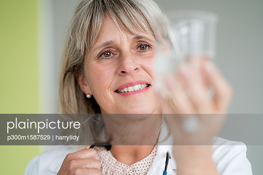 Smiling mature woman holding glass of water - p300m1587529 von harrylidy