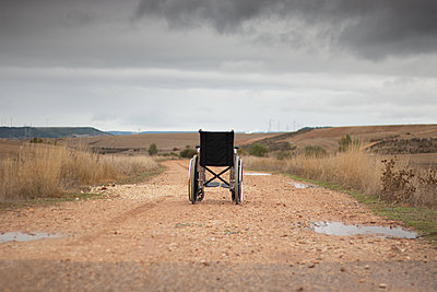 Rear vision of a wheelchair isolated in the middle of a path - p1166m2146697 by Cavan Images