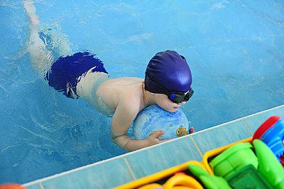 The boy learn to swim in the indoor pool - p1412m1466347 by Svetlana Shemeleva