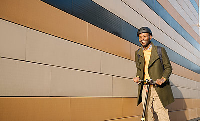 Happy man with helmet and scooter passing a building - p300m2154599 by Hernandez and Sorokina