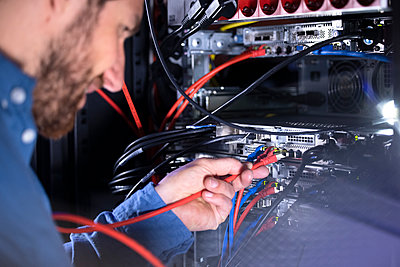 Male IT specialist installing patch cord cable in server rack in data center - p300m2274628 by Florian Küttler