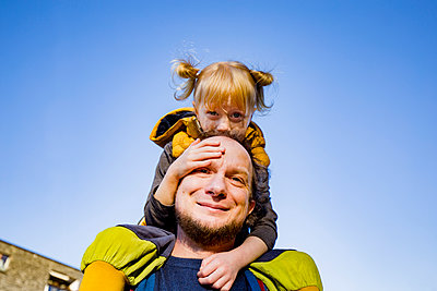 Smiling man piggybacking blond daughter against sky - p300m2275449 by Irina Heß