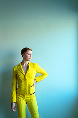 Young woman wearing yellow pantsuit - p427m2109255 by Ralf Mohr