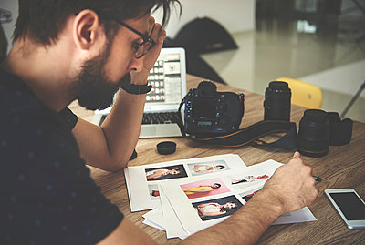 Stressed photographer looking at photographs in photography studio - p429m1418192 by Gpointstudio