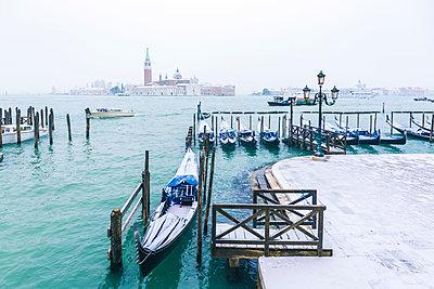 Gondolas with snow at St Mark's waterfront, Venice, Veneto, Italy. - p651m2034018 by Marco Bottigelli