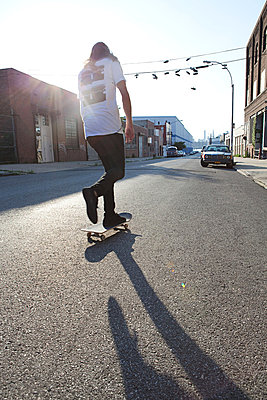 Skateboarder on urban street in sunlight - p9245196f by Image Source