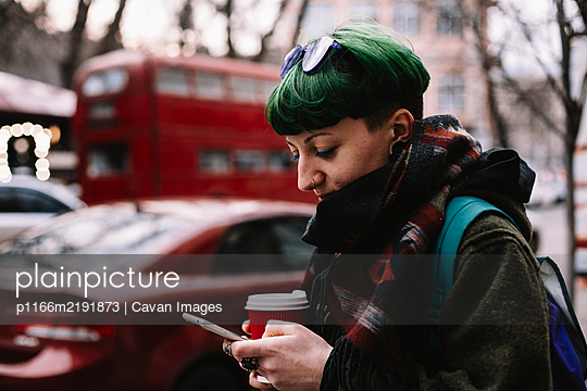 Portrait of non-binary hipster using smart phone standing in city - p1166m2191873 by Cavan Images