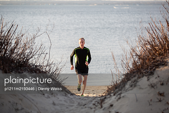 Senior athlete jogging on the beach - p1211m2193446 by Danny Weiss