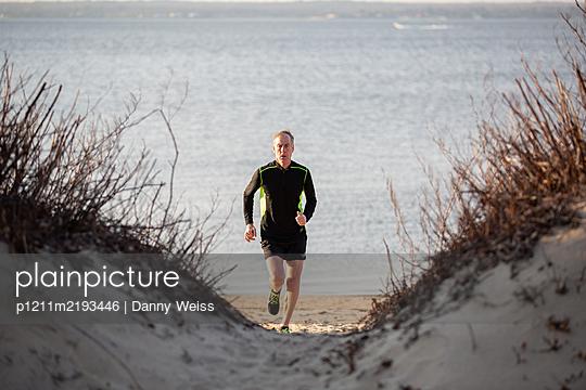 Älterer Sportler beim Joggen am Strand - p1211m2193446 von Danny Weiss