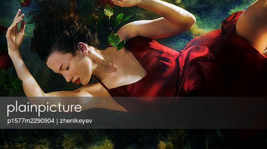 Junge Frau in rotem Kleid unter Wasser - p1577m2290904 von zhenikeyev