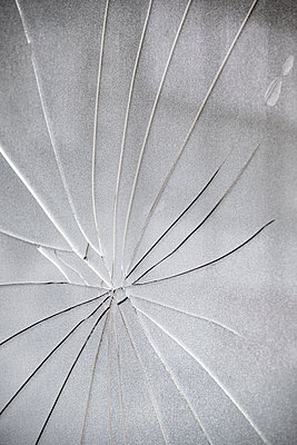 A large cracked spreading across a broken window in a web like structure from the impact point. - p1057m2141779 by Stephen Shepherd