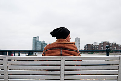 young man sitting on a bench staring at the city with a serious face - p1166m2234416 by Cavan Images