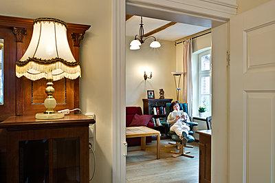 Senior woman reading book in living room - p227m1589149 by Uwe Nölke