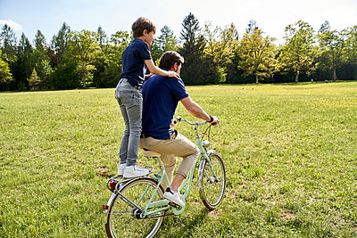 Father and son enjoying bicycle ride on grass during sunny day - p300m2197447 by Stefanie Aumiller