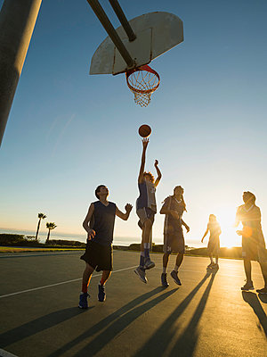 Back lit basketball teams playing on court - p555m1415529 by Erik Isakson