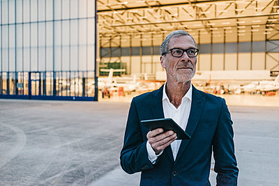 Mature businessman with tablet computer in front of hangar - p586m1208532 by Kniel Synnatzschke