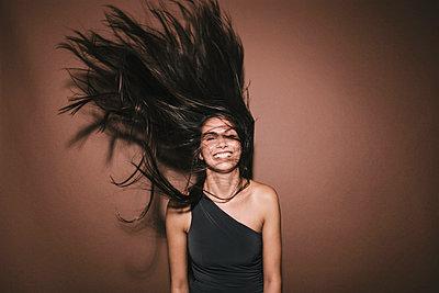 Junge Frau schüttelt ihre langen dunklen Haare - p586m953769 von Kniel Synnatzschke