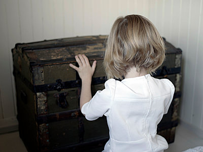Blonde girl opening old chest - p945m1446196 by aurelia frey