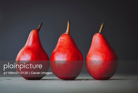Close-up of red pears side by side on table - p1166m2112120 by Cavan Images