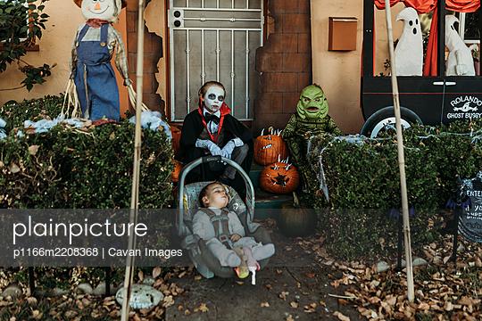 Three male siblings dressed in Halloween costumes posing at home - p1166m2208368 by Cavan Images