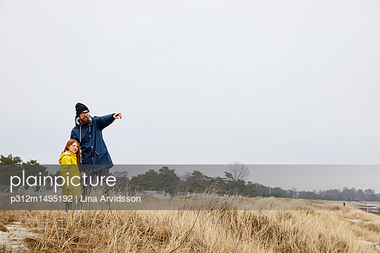 Father and daughter on beach - p312m1495192 by Lina Arvidsson