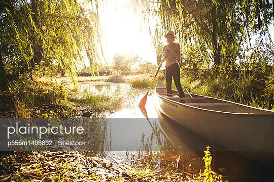 Caucasian woman rowing canoe in rural creek - p555m1408892 by Shestock