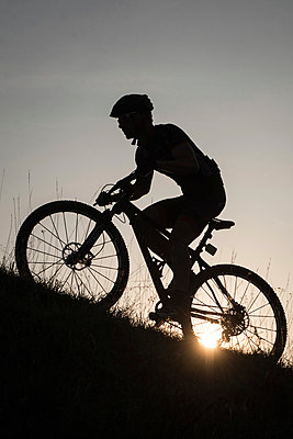 Man riding mountain bike in nature in the Bologna countryside, Italy - p307m937558f by Enrico Calderoni