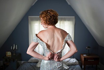 Woman in bedroom unzipping evening gown - p429m839073 by Zave Smith