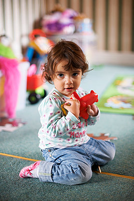 Female toddler sitting on playroom floor playing with a red toy - p429m896524f by Peter Muller