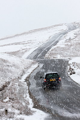 A car negotiates a road through a wintry landscape in the Elan Valley area in Powys, Wales, United Kingdom, Europe - p871m1136151 by Graham Lawrence