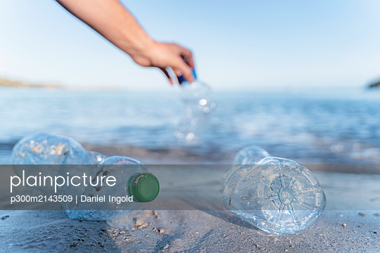 Hand collecting empty plastic bottles at seashore - p300m2143509 by Daniel Ingold