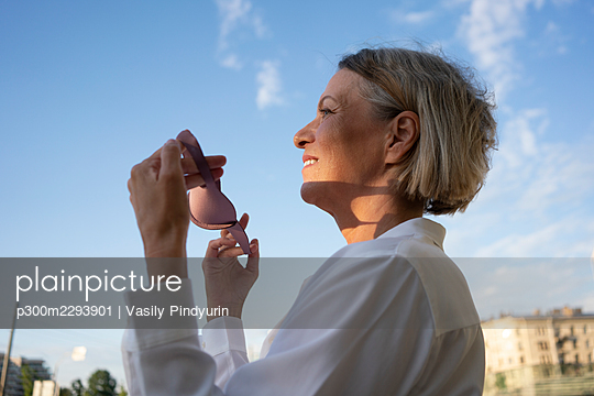 Mature businesswoman with sunglasses standing by sky - p300m2293901 by Vasily Pindyurin