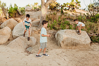 Three young brothers dancing in sunny California cactus garden - p1166m2136689 by Cavan Images