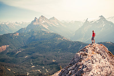 Man in red standing on summit looking out at the view. - p1166m2269420 by Cavan Images