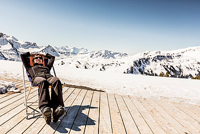 Austria, Damuels, woman relaxing in deckchair on sun deck in winter landscape - p300m1505765 by Nullplus
