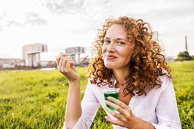 Germany, Cologne, portrait of happy young woman eating jelly on meadow - p300m2069817 by Jo Kirchherr
