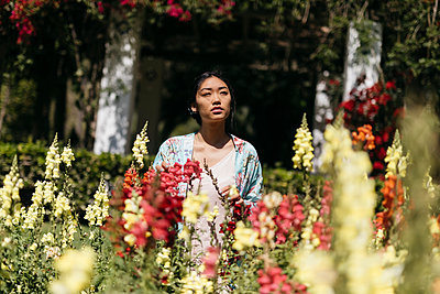 Young asian woman surrounded by flowers playing with shadows on her face - p300m2167553 von Tania Cervián