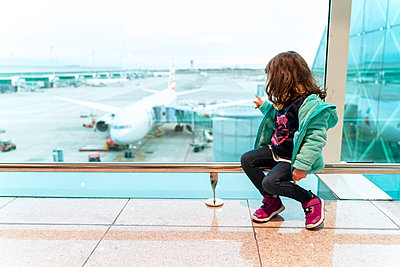 Girl sitting at the airport in front of a plane, ready to travel - p300m2170180 by Gemma Ferrando