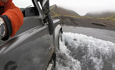 Jeep driving through deep puddle - p42917814f by Thorsten Henn